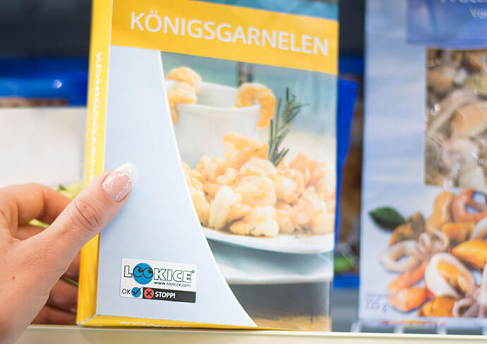 Woman takes frozen shrimp with LOOKICE label from the freezer in the supermarket